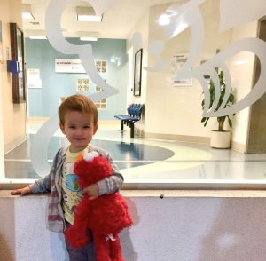 Crosby, hugs Elmo stuffed animal. He lives with Morquio A Syndrome, a very rare metabolic disease