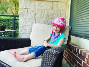 Felicity Frugé sits on a large patio chair and smiles