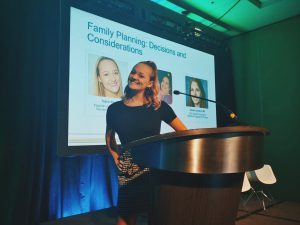 Taylor Kane stands behind a podium at the Global Genes conference.