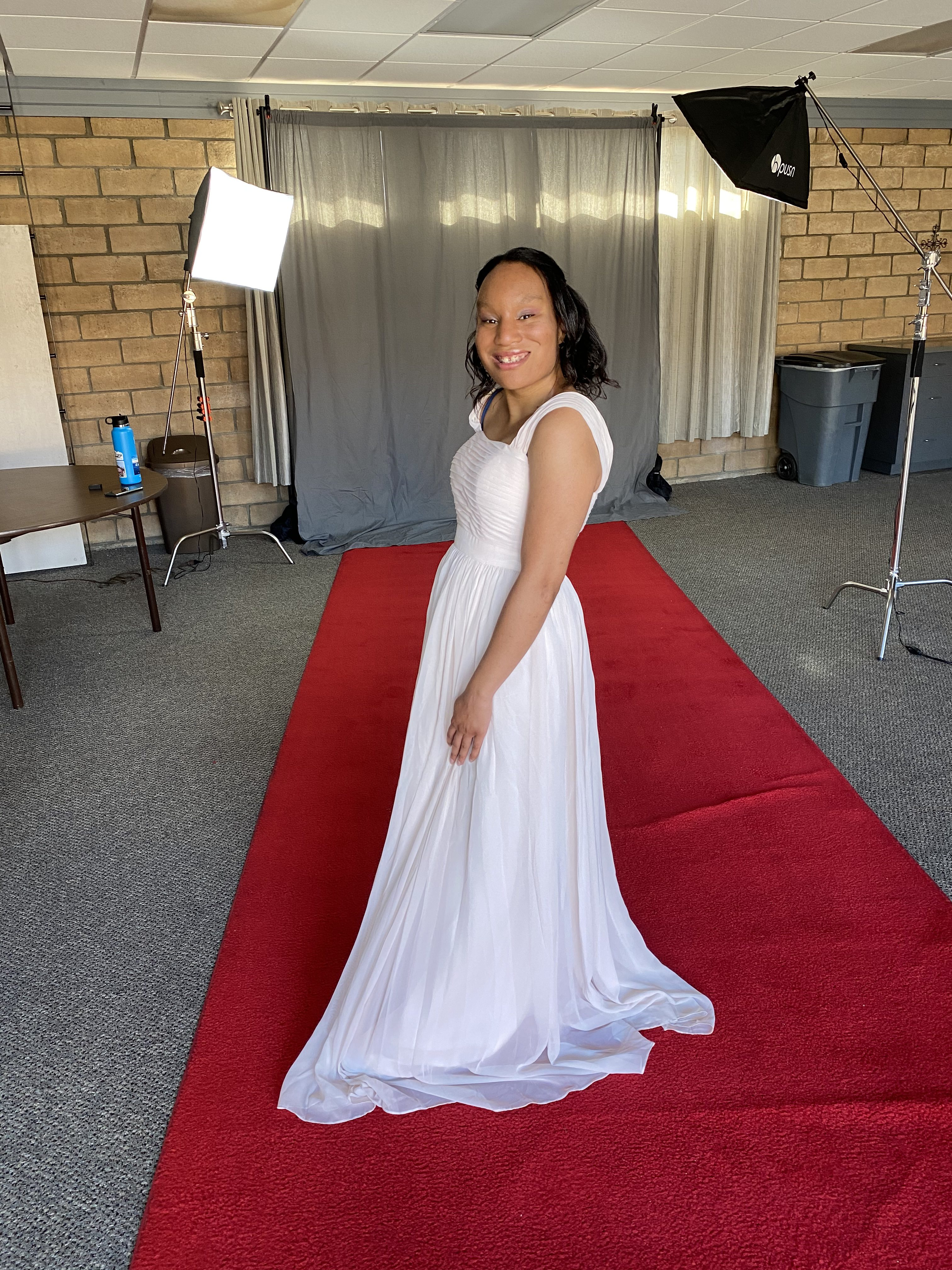 Saida Mahoney, a rare disease advocate, wearing a white dress and smiling for a photo on a red carpet with a gray curtain in the background for the California Miss Amazing pageant.